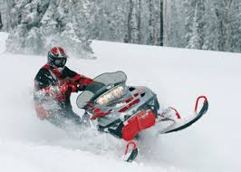 red snowmobile racing on white snow