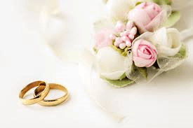 Two gold wedding bands laying next to pink and white rose bouquet